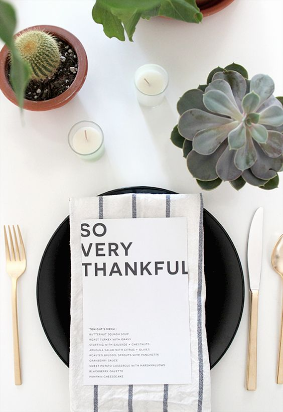 a modern Thanksgiving tablescape with black plates, gold cutlery, candles, succulents and cacti