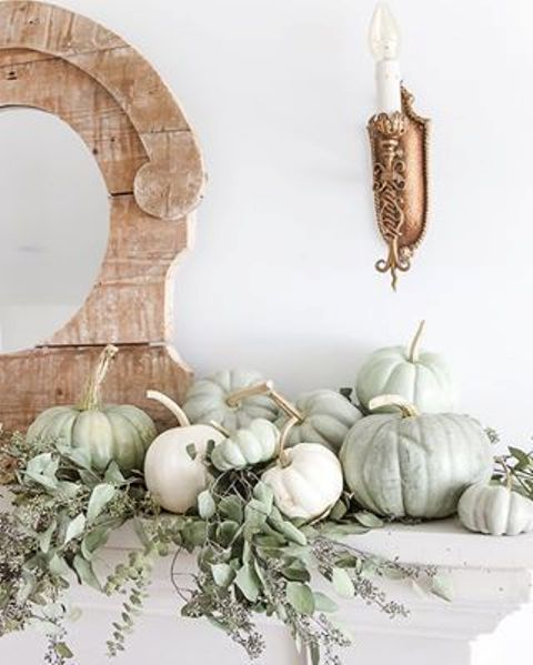 an arrangement of white and light green pumpkins and some lush greenery are all you need for a cool look