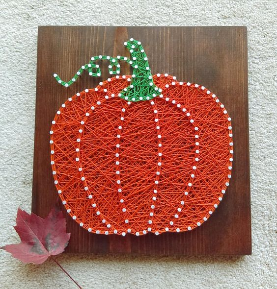 a colorful pumpkin string art with white nails looks unusual