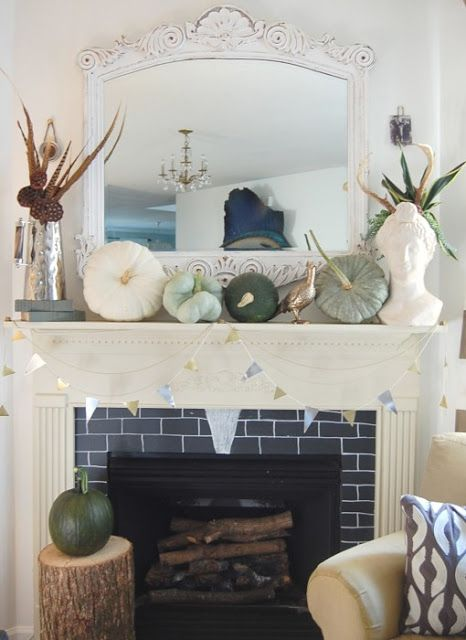 a mantel with green and white pumpkins, feathers and pinecones arranged