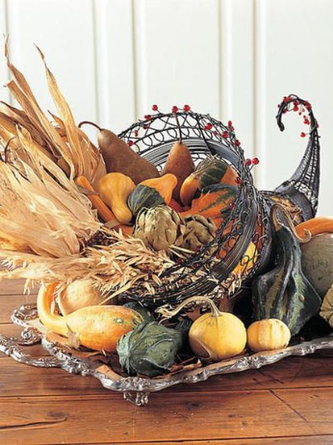 a metal cornucopia with red beads filled with gourds, pumpkins, pears and corn husks