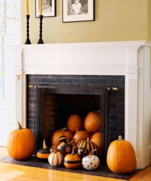 a stylish pumpkin display in the fireplace, all pumpkins are painted differently
