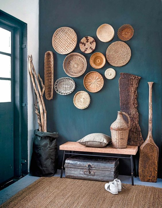 a teal entryway is made rustic and welcoming with baskets on the wall, a crok bench and a jute rug