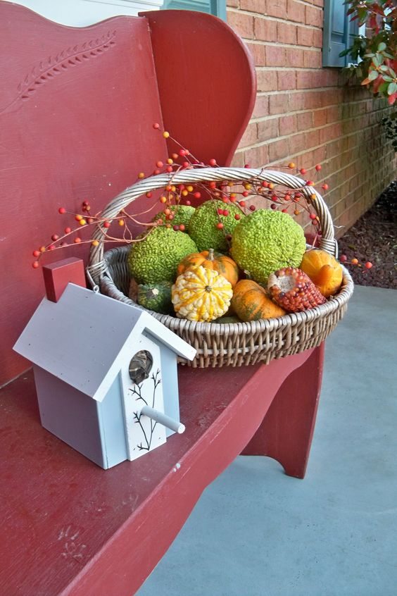 a basket with peas balls, corn and faux gourds and pumpkins for a porch