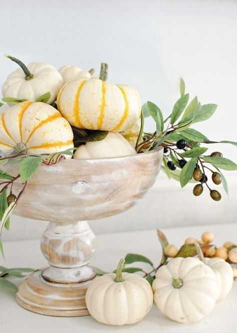 a whitewashed bowl with pumpkins and olive branches with olives