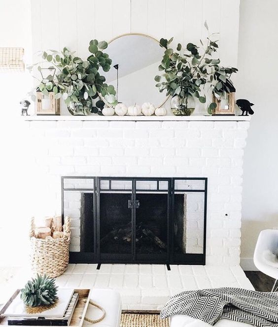 lanterns, white pumpkins, lush foliage for a neutrla modern mantel