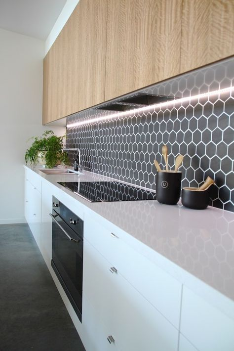 white cabinets below and wooden hanging ones are accentuated with lights and a hexagon backsplash