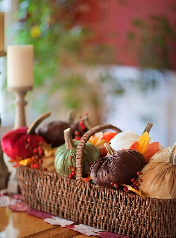 a basket with pumpkins of colorful fabric, faux leaves and berries for a rustic look