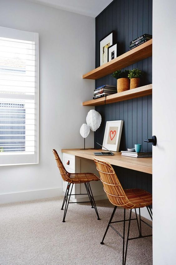 a chic Scandinavian space with a wall-mounted desk, matching shelves and wicker chairs