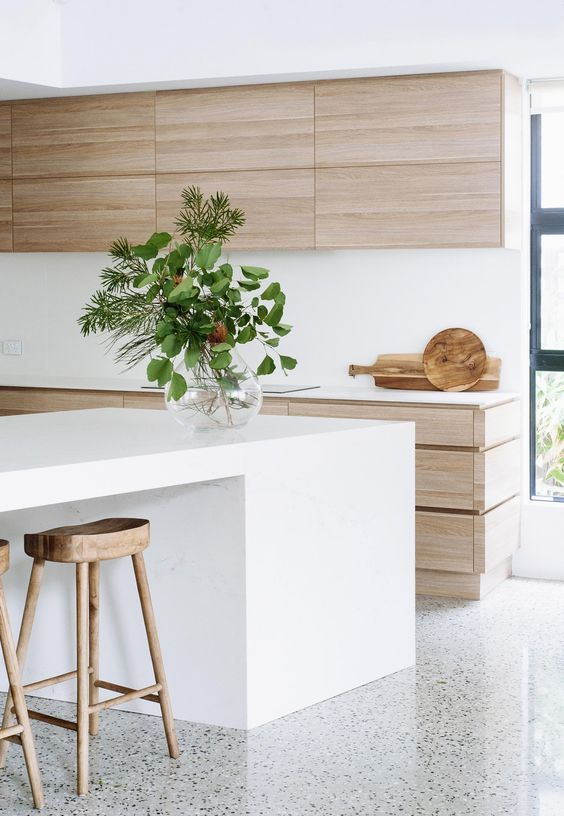 a light-colored wood kitchen is made more modern with a white kitchen island and white countertops
