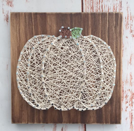 a neutral string art pumpkin with a gree and brown stem on a wooden board