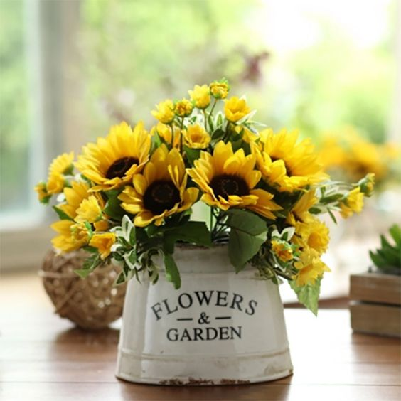 a sunflower arrangement in a vintage bucket looks simple and farmhouse-like