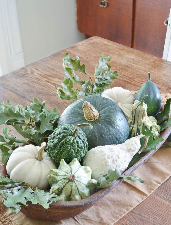 a vintage bowl with gourds, pumpkins and zucchini and oak leaves looks very rustic