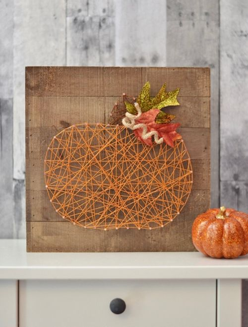 a cool string art pumpkin wall art topped wit faux leaves and a twine stem