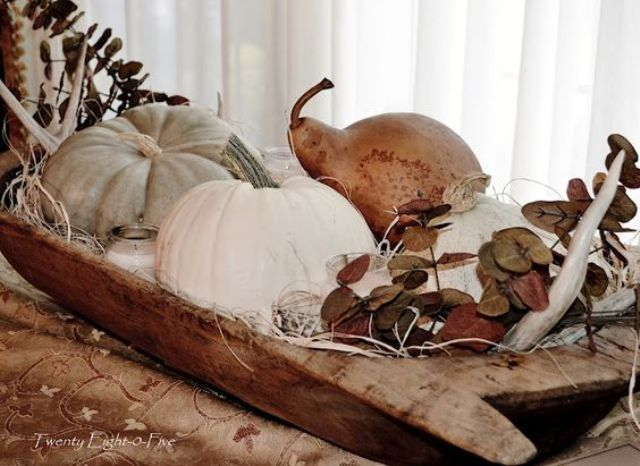 a dough bowl with pumpkins, pears, dried leaves and a candle