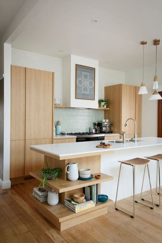 a light-colored wood kitchen with a white kitchen island and open shelving of wood