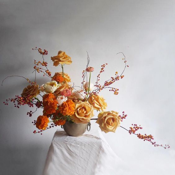 orange, peachy shades and cream for a refined Thanksigivng floral arrangement that is perfect for a mantel decor