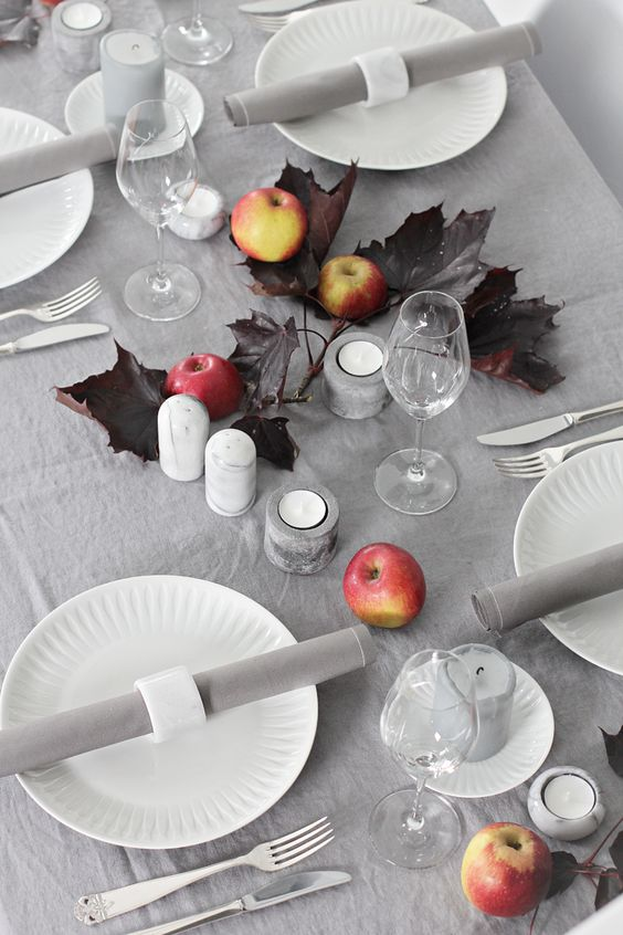 stylish, minimalist autumnal table setting with apples, candles and dark leaves looks wow