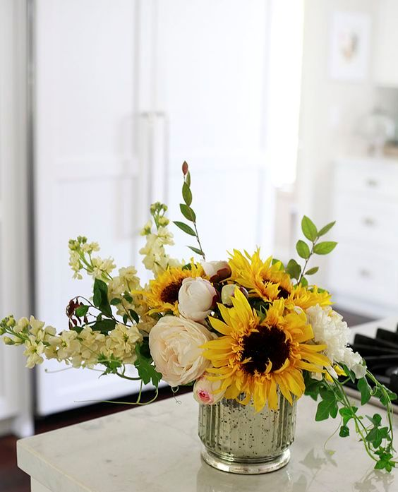 a bold arrangement with sunflowers, white blooms and greenery will add fall colors