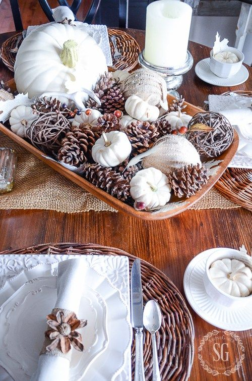 a dough bowl with white and fabric covered pumpkins, pinecones and wicker balls