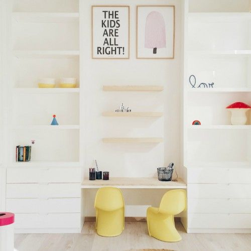 a modern and playful space done in creamy white with shelves, drawers and two curved chairs for the little ones