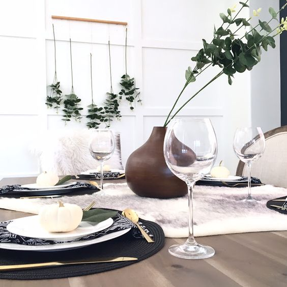 a modern fall look with black placemats, eucalyptus, a faux fur table runner and white pumpkins is simple to recreate