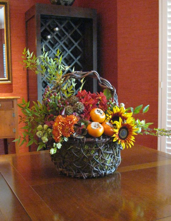 a basket with moss and an arrangement of persimmons, greenery and bold faux blooms