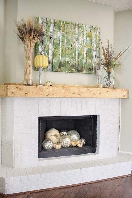 a chic mantel with wheat, feathers and pumpkins and some pumpkins inside the fireplace