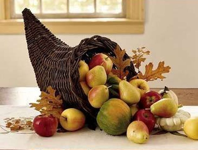 a cornucopia filled with fall fruit and leaves can be a cool centerpiece
