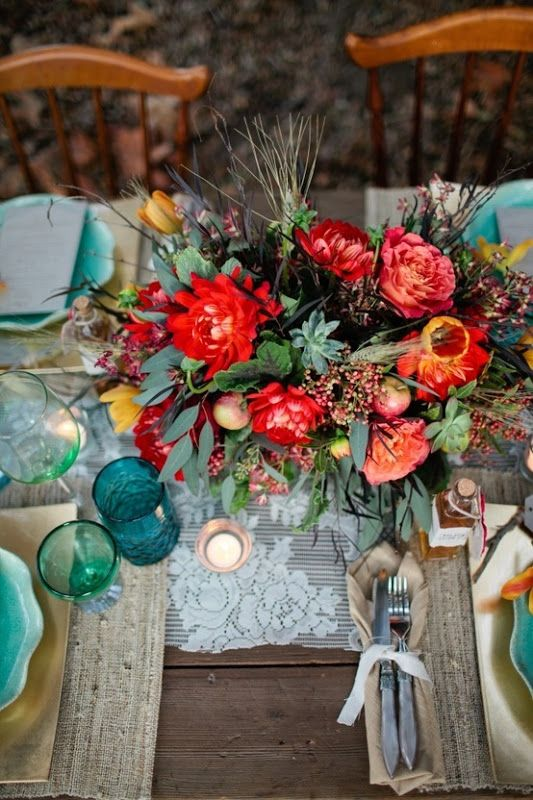 a floral centerpiece with greenery, succulents, wheat, red and yellow blooms for a coastal Thanksgiving