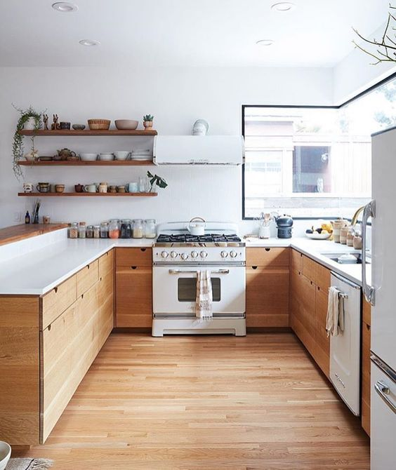A Kitchen Of Natural Wood And White Countertops Liances Looks Very Inviting
