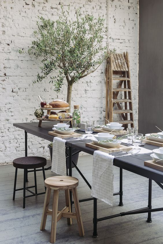 a modern table setting with a black table, light-colroed wood boards and olive branches