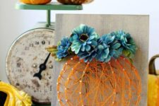 09 a wood sign with an orange string art pumpkin topped with blue flowers