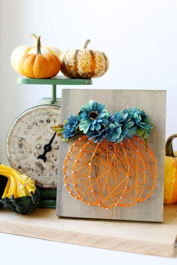 a wood sign with an orange string art pumpkin topped with blue flowers