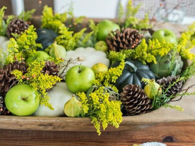 a bowl with green apples, pinecones, white and dark green pumpkins and greenery