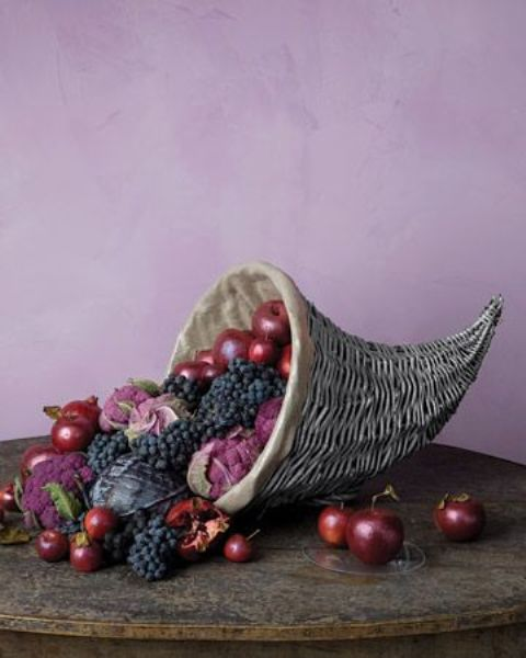 a chic cornucopia with apples, grapes, cabbage looks moody and very chic