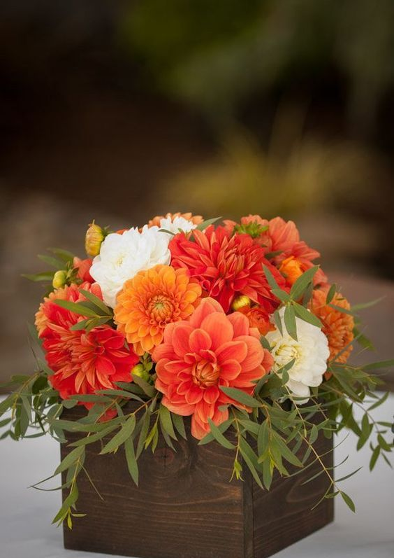 a fall outdoor arrangement with orange, red and white blooms and greenery in a wooden box