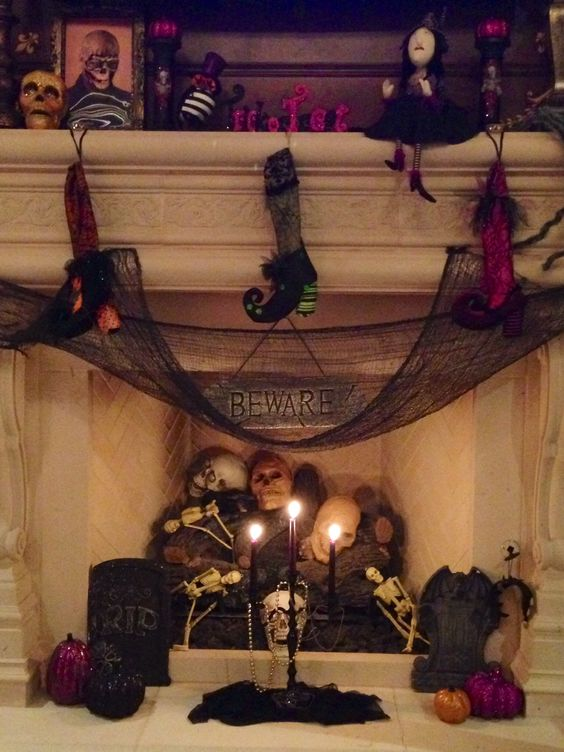 a faux fireplace with skulls, skeletons and candles