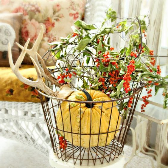 a metal basket with a large pumpkin, berries, greenery and antlers for a cool forest inspired look