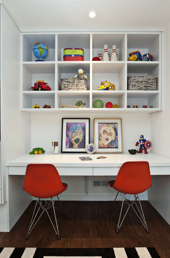 a modern study and art space for two, shelves for storing toys and bold red chairs
