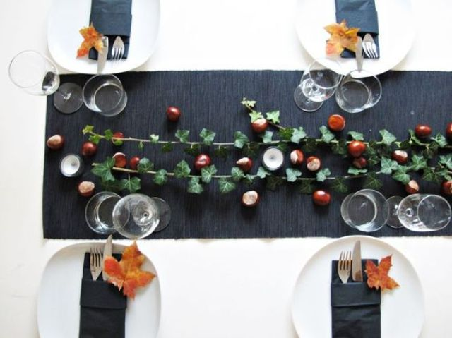a chic fall tablescape with a black table runner, acorns, foliage and fall leaves