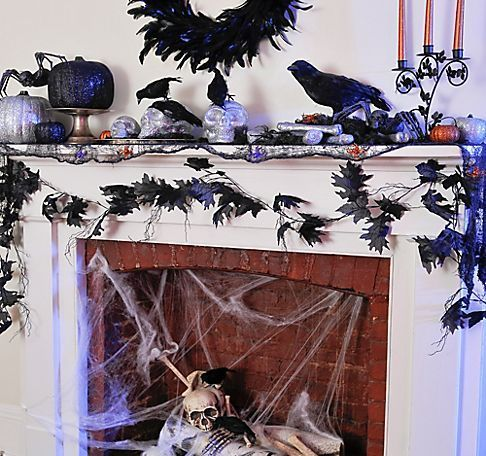 a fireplace with spider webs, faux birds and skulls with the same on the mantel