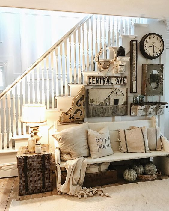 a vintage whitewashed wooden bench and some baskets makes the entry rustic