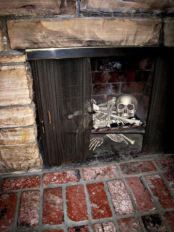 a human skeleton and a skull inside a fireplace is a scary idea for Halloween