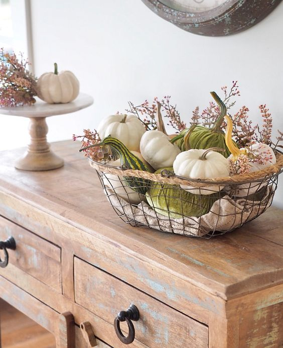 a metal basket with real and velvet pumpkins and gourds and some dark flowers