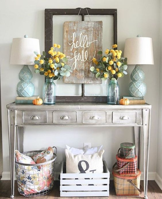 a whitewashed wooden console, a vintage frame and crates create a light rustic space