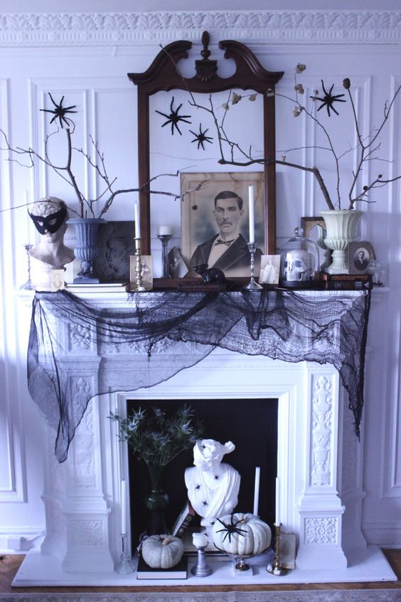 a black and white display with a pumpkin, a statue, thistles, candles