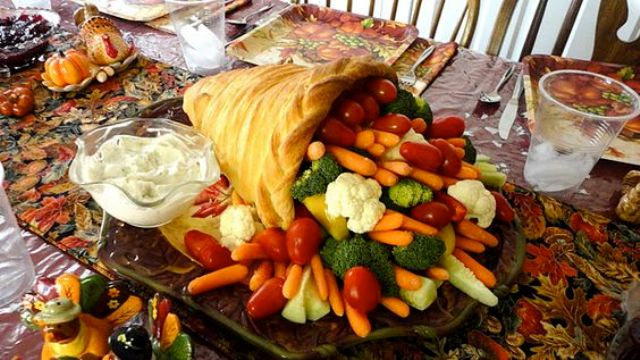 a bread cornucopia filled with fresh vegetables and a dip in a bowl next to it