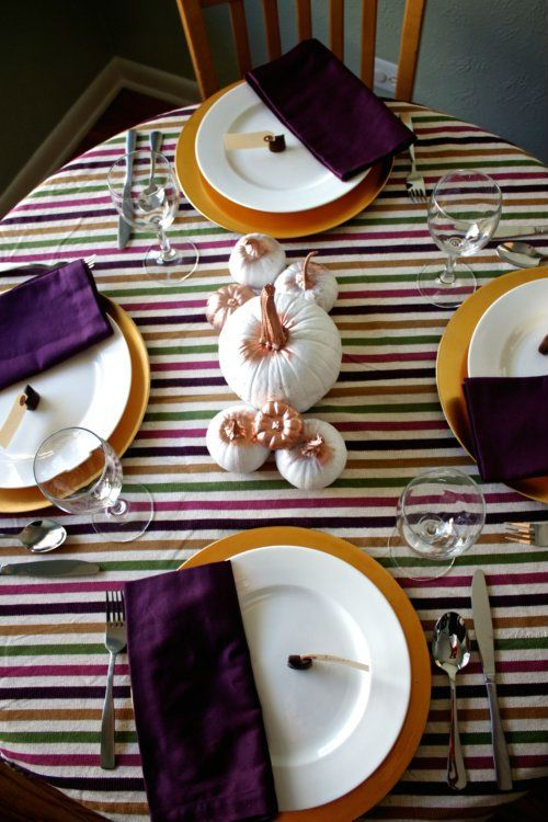 a colorful tablescape with a striped tablecloth, purple napkins, white and gold pumpkins