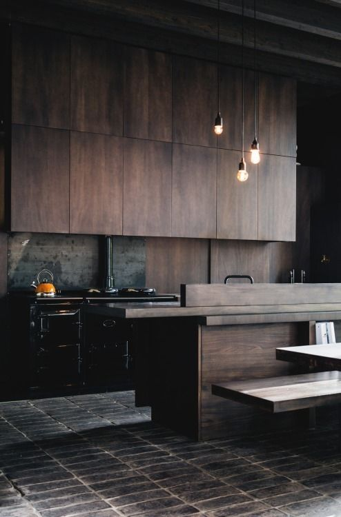 a dark and moody modern kitchen with dark-colored wood cabinets and black appliances